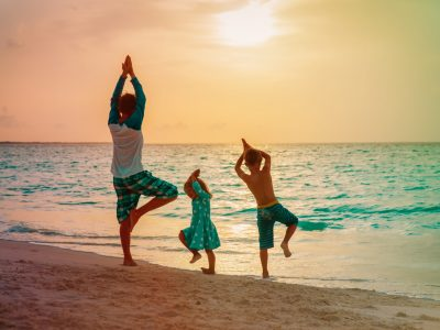 father with kids exercise at sunset beach, family doing yoga at sea