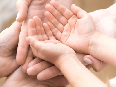 Close up of three caucasian person stack their palms. Grandmother mother and granddaughter holding their hands together. Gesture sign of support and love, unity togetherness relative people concept
