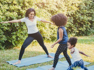 Black African American mom with childs playing yoga family activity together at backyard during self quarantine at home.